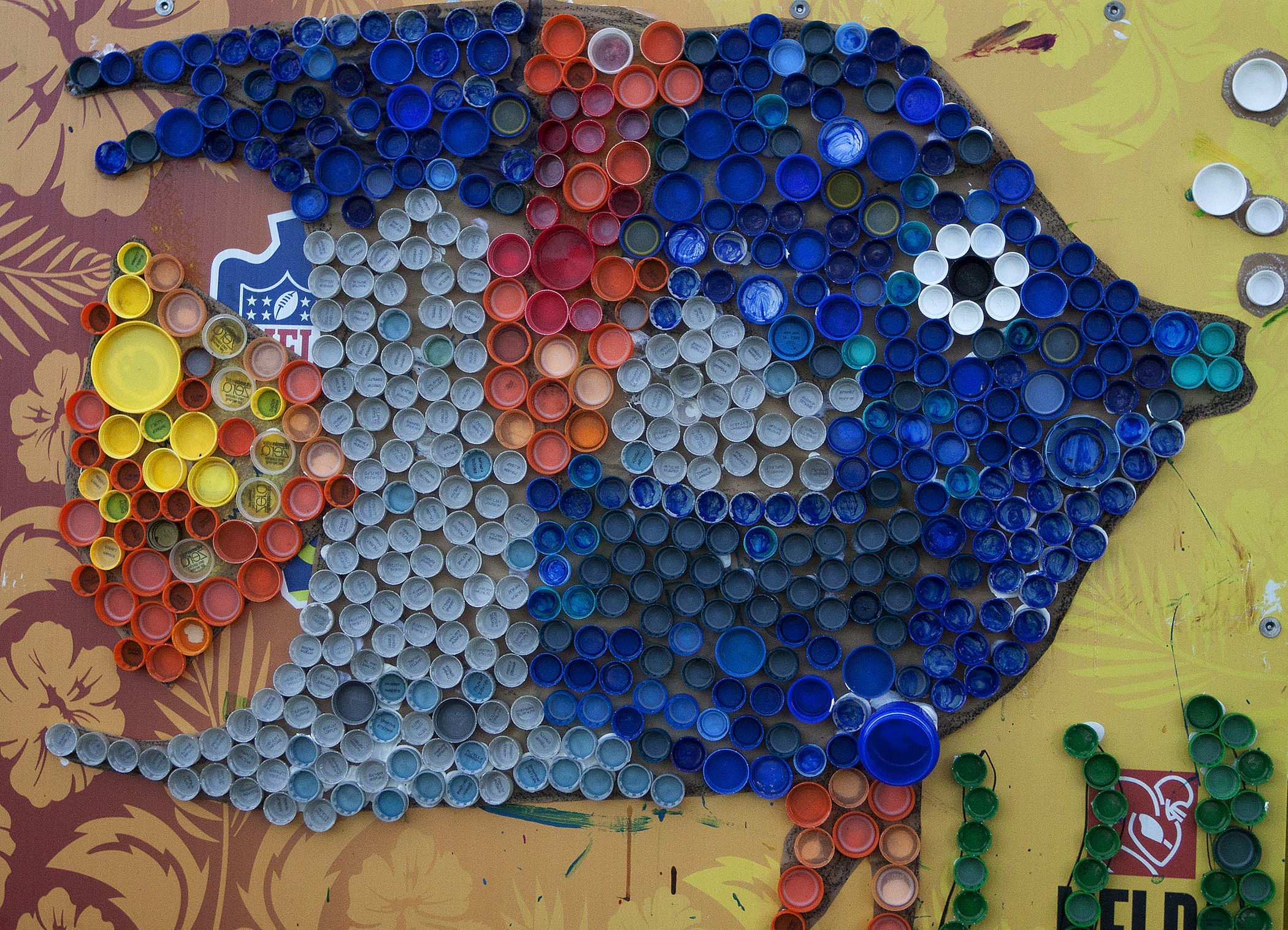 "A piece of artwork is made of recycled bottle caps pasted together by children near Riseley Field at Marine Corps Base Hawaii, April 16, 2013. The finished piece will go on display during the Earth Day Expo April 20, 2013 to show the creativity of the children who attended ""Eco-Friendly In the Park."" (U.S. Marine Corps photo by Lance Cpl. Matthew Bragg)"