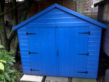Tiger Bike Store painted blue and placed in a garden
