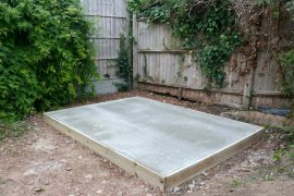 Dried concrete shed base with shed frame