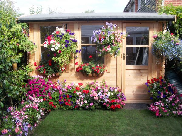 This customer kept their log cabin unpainted but brought some colour the building with hanging baskets and colourful flowers surrounding the cabin.
